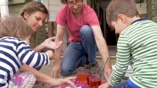 Mladá rodina s dětmi pracovat na zábavný společný projekt umění a řemesla
