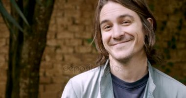 Handsome man with long hair smiling and looking at the camera