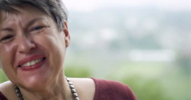 Healthy retired woman in her 60s laughing out loud