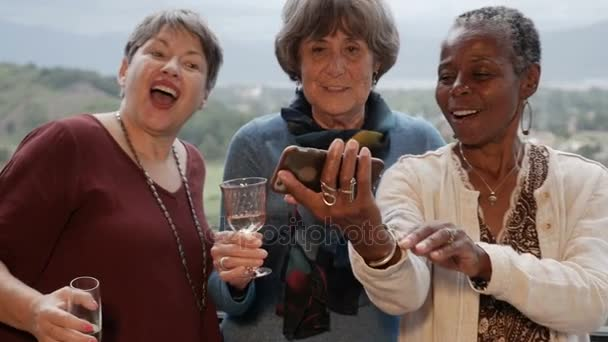 Diverse group of multi racial senior women take a selfie with smartphone