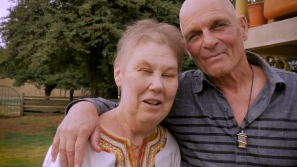 Šťastný pár starších senior 70 s úsměvem a při pohledu na fotoaparát