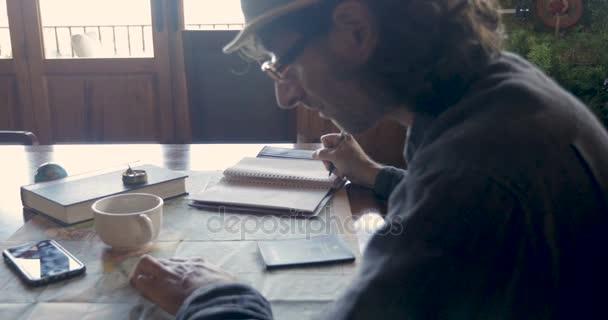 Člověk při pohledu na hledání mapa světa cestovních destinací a psaní v knize