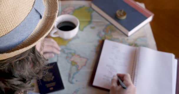 Overhead of man planning a trip of a lifetime and writing in journal