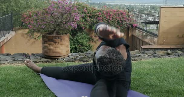 Flexible senior African American woman doing sitting yoga poses and stretches