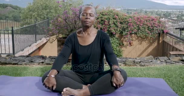 Retired African American woman resting quietly on a yoga mat meditating