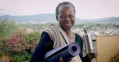 Mosolygó idős afroamerikai vezető tartó női jóga mat és a vizes palack