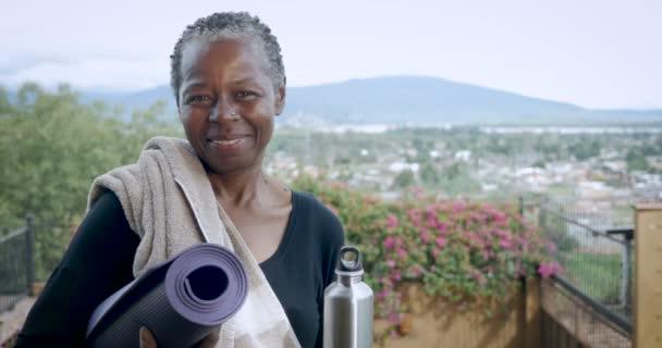 Afro-amerikai vezető nő mosolyogva és nevetve a gazdaság jóga mat portré