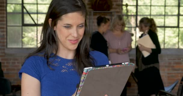 Woman working on tablet looking at camera smiling in front of female coworkers