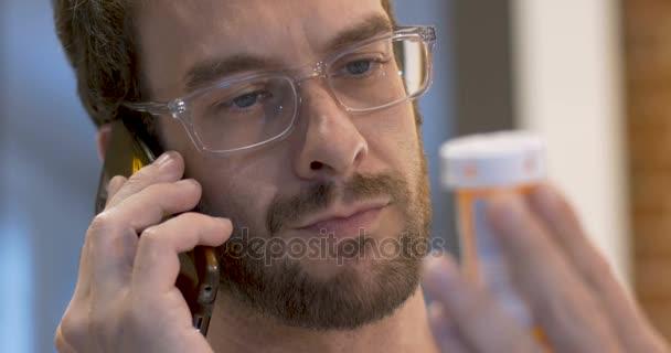 Šťastný mladý dospělý muž doplňování jeho předpis na svém mobilním telefonu