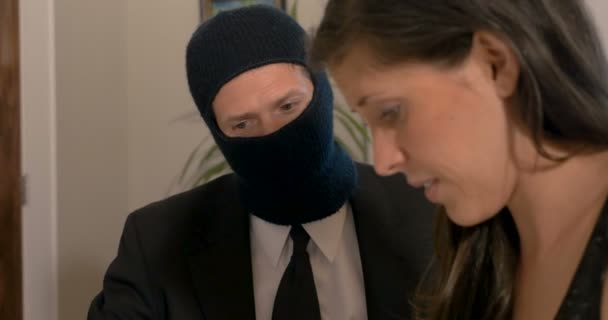 Man wearing a ski face mask and suit and tie getting a woman to sign paperwork