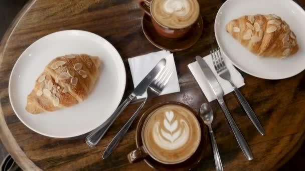 Režijní náklady na gurmánské snídani s luxusní kávu a croissanty na dřevěný stůl