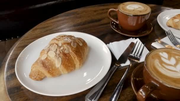 Nízký úhel latte umění a mandle croissanty na tmavý dřevěný stůl