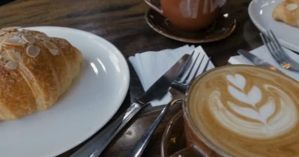 Přenesme se přes kávu latte umění a mandle croissanty na stůl v kavárně