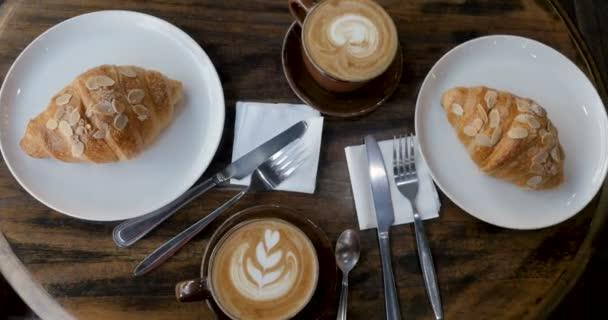 Režie dvou šálků kávy a dva zákusky na jídelní stůl