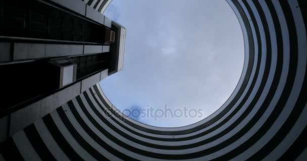 Establishing shot of the sky seen through a round futuristic skyscraper