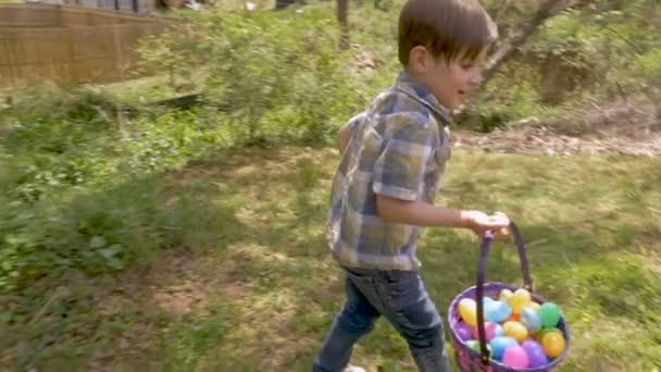 Happy excited young 4 - 5 year old boy holding a basket filled with easter eggs