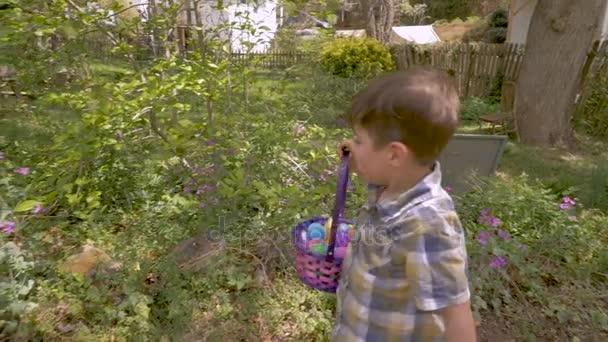 Happy smiling little boy finding easter eggs during a easter egg hunt