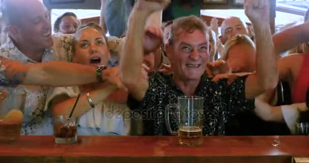 Group of friends having fun celebrating and watching sports in a bar
