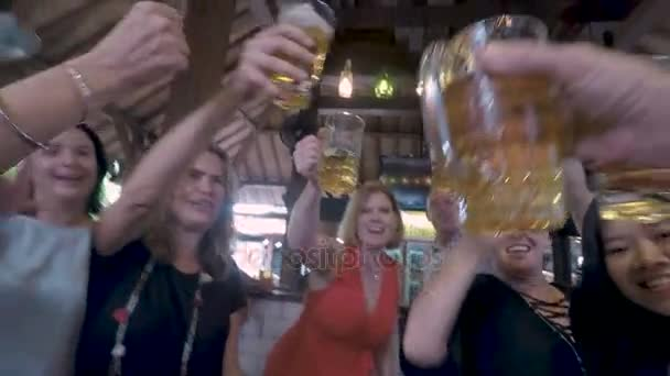 POV of a group of people toasting and cheering a man holding a beer glass