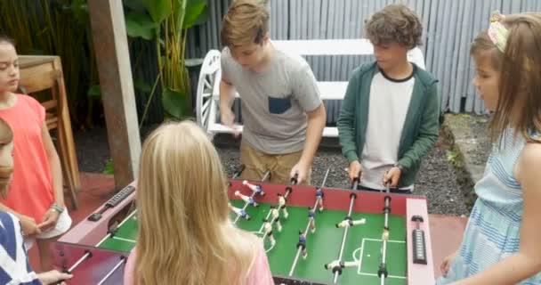 Mladé dívky proti mladí chlapci hrají fotbal a dívky skóre vyhrát