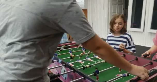 A young pre teen girl plays foosball with her friends