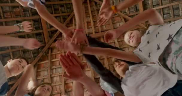 Heterogene Gruppe von jungen und Mädchen, indem ihre Hände in der Mitte ein jubeln zu tun