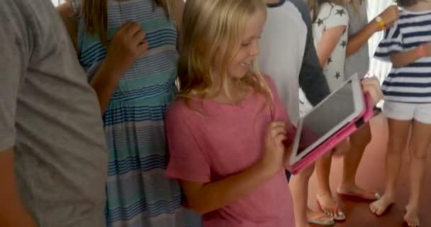Velká skupina mladých chlapců a děvčat, tablet a chytrý telefon technologie sdílení
