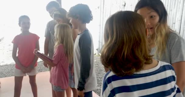 Smíšené rasové skupině mladých chlapců a dívek mluví a sdílení technologií