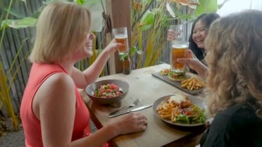 Three beautiful young women laughing and celebrating over a meal and drinks