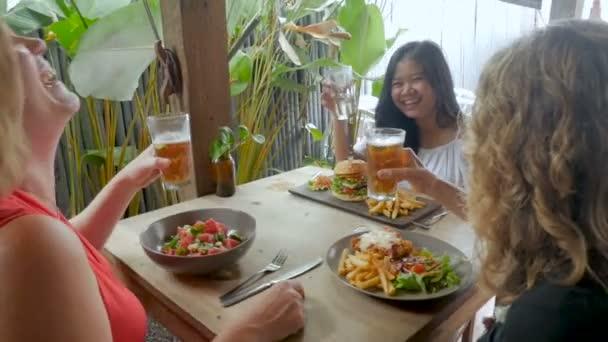 Drei verschiedene Frauen lachen und feiern mit Getränken und Mittagessen