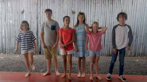 Happy diverse group of young children standing next to each other in a line