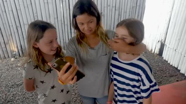 Mladá dívka pokrývající ústa přátel při pořizování selfie s chytrý telefon