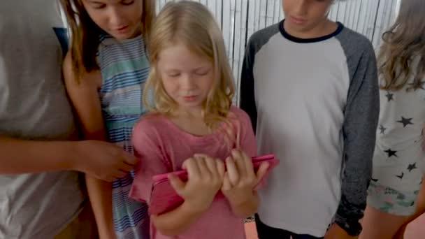 Happy různorodá skupina mladých chlapců a dívek pohromadě při pohledu na digitální tabletu