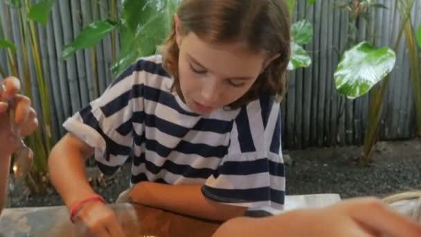 Zblízka mladé 11-12 let stará dívka dostává lžíci dezert