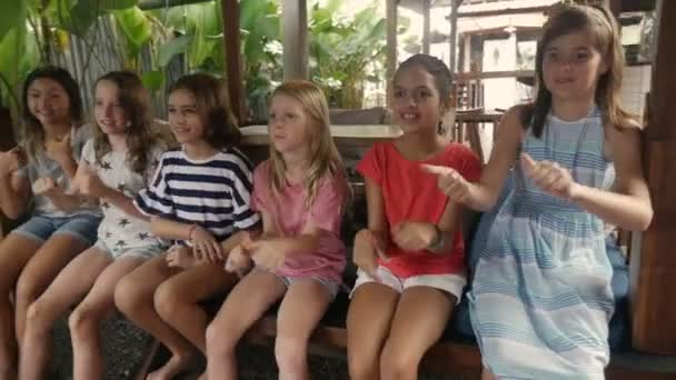 Bunte Gruppe fröhlicher junger Mädchen, die Daumen hoch und Stuhl tanzen
