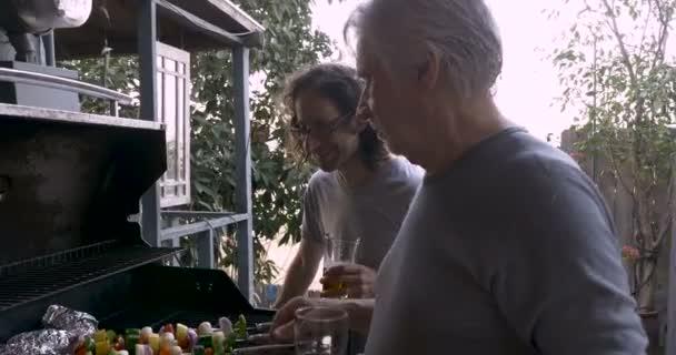 Starší otec a syn spolu grilování zeleniny kotlety na grilu