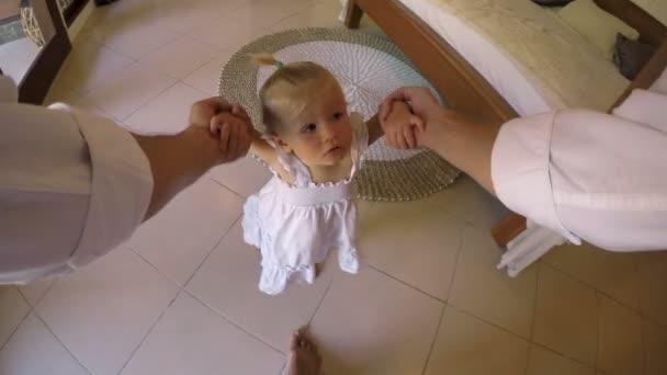 POV roztomilý mladý baby Girl bere její první chodící kroky se svým otcem