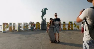 Man photographs two tourists in front of the Puerto Vallarta art sign in Mexico