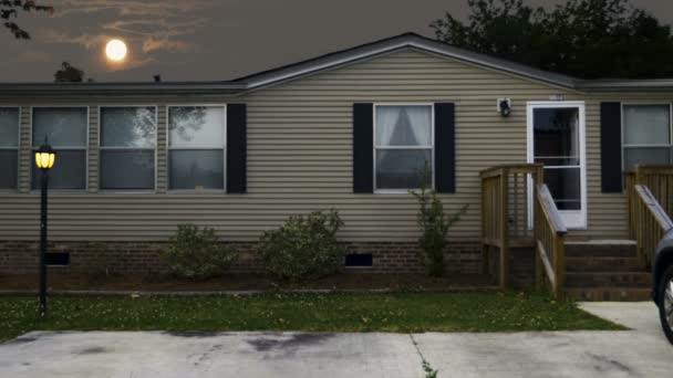 Establishing shot of a manufactured home with a full moon rising over its roof