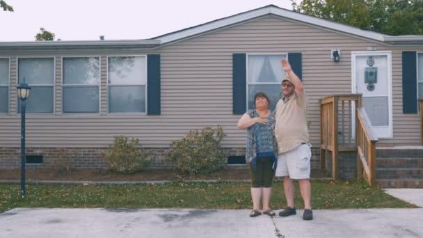 Schweres Paar winkt und verabschiedet sich von jemandem vor seinem Haus