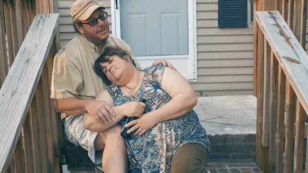 Happy overweight couple sitting on porch steps resting in each others arms