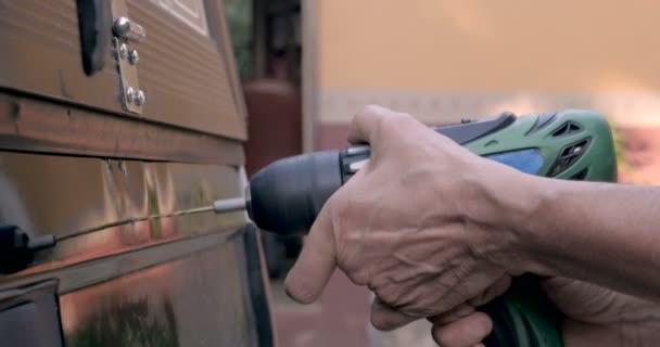 Detailní záběr ruky držící akuvrtačku vrtání do zadní části náklaďáku