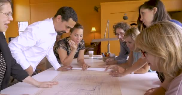 Diverse group of men and women looking at blue prints in contemporary office