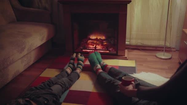 Nohy z vlněné ponožky vánoční krbu. Detailní záběr na nohy. Zimní a vánoční svátky koncept.