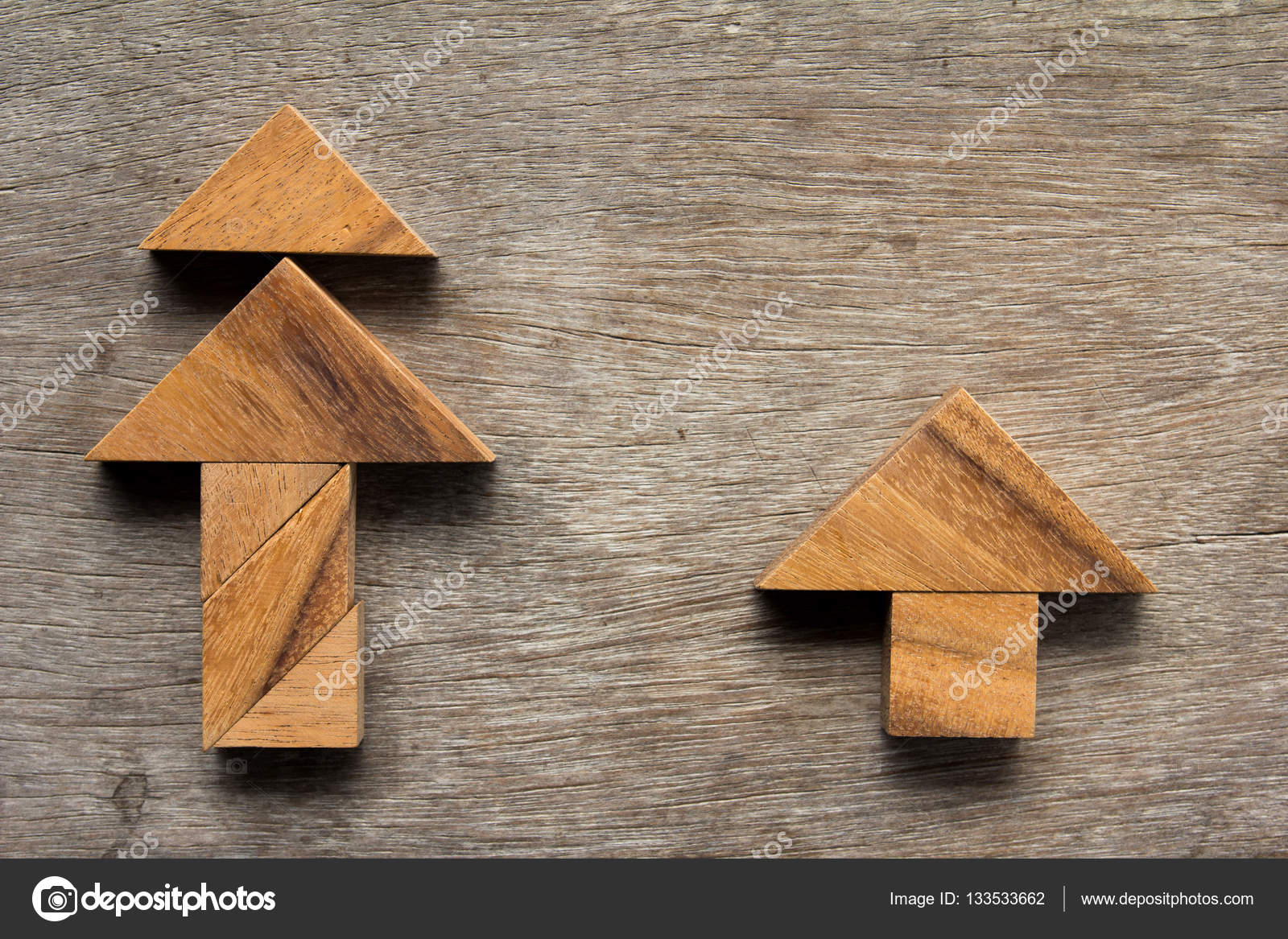 wooden tangram as christmas tree and home shape on old wood back stock photo