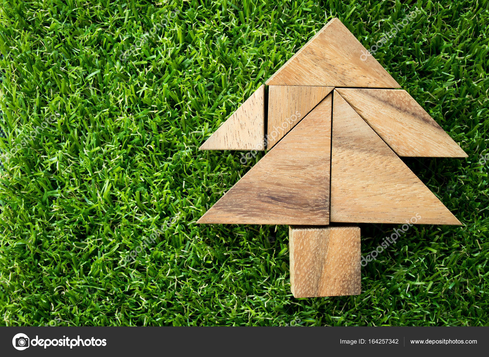 wood tangram puzzle in christmas tree shape on artificial green grass background stock photo