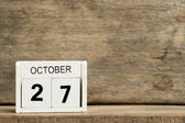 Photo White block calendar present date 27 and month October on wood background