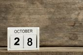 Photo White block calendar present date 28 and month October on wood background