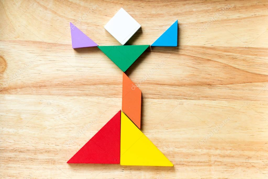Color tangram puzzle in singing man shape on wood background