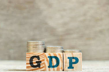 Block in word GDP (Gross domestic product) with coin in decrease trend on wood background